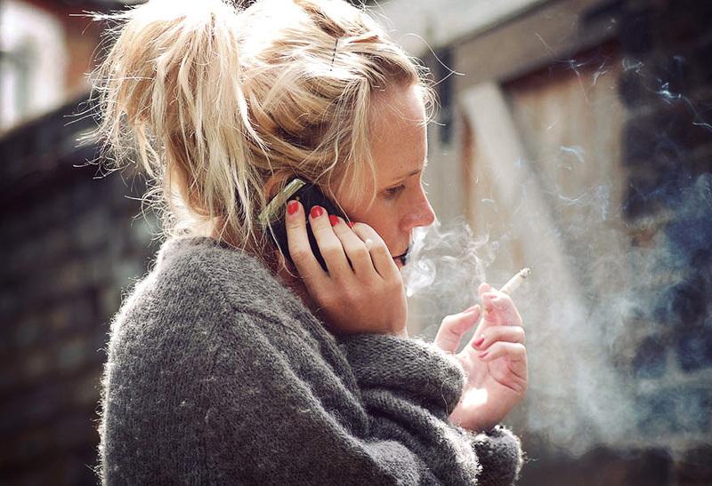 frau raucht und telefoniert